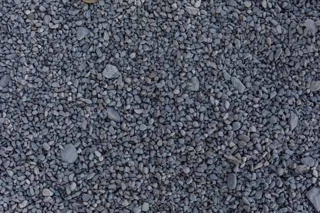 Pequeñas piedras grises para construcción en el suelo.