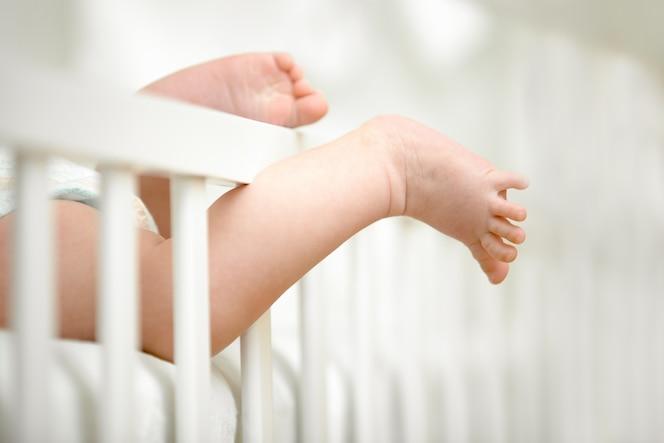Pequeñas piernas atrapadas entre el marco de la cuna