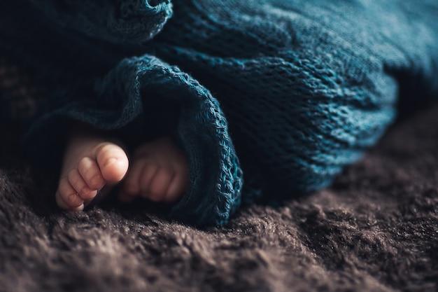 Las pequeñas piernas del bebé recién nacido asoman por debajo de la manta.