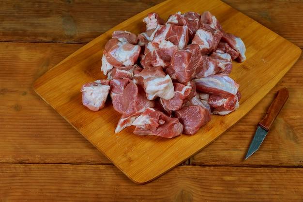 Pequeñas piezas de carne de res cruda con cuchillo en una tabla de cocina.