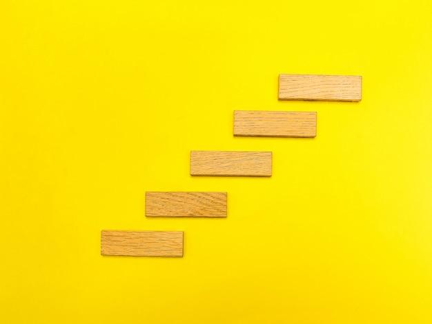 Pequeñas piezas de madera sobre superficie amarilla