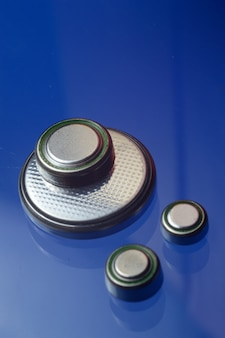 Pequeñas pilas de botón de diferentes tamaños, resaltadas en rojo y naranja, se encuentran sobre un fondo azul. de cerca.