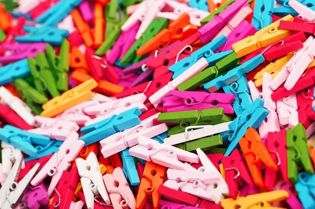 Pequeñas pinzas de ropa multicolores como una textura de pantalla completa y fondo. pinzas decorativas para la creatividad.