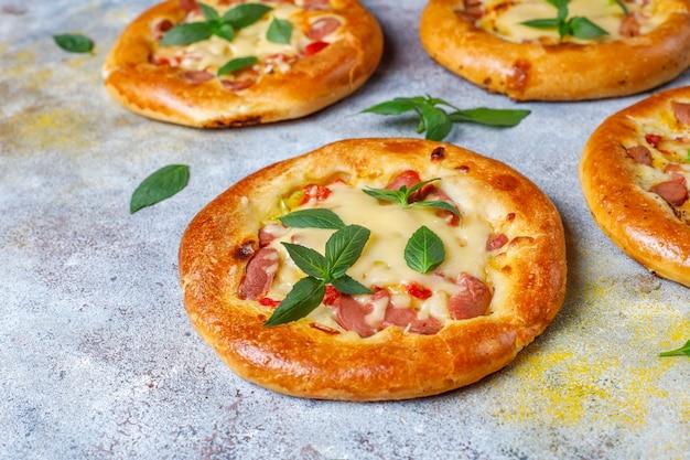 Pequeñas pizzas caseras frescas con albahaca.