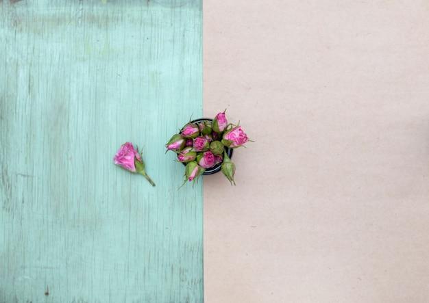 Pequeñas rosas rosadas en la superficie de madera y papel artesanal