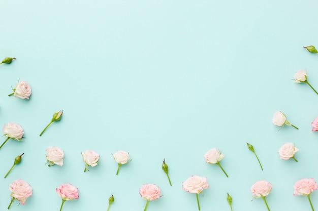 Pequeñas rosas sobre fondo azul con espacio de copia