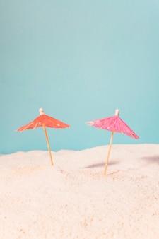 Pequeñas sombrillas para bebidas en arena.