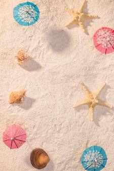 Pequeñas sombrillas con conchas en la playa.
