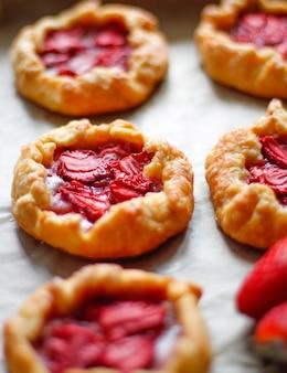 Pequeñas tartas rústicas de tarta de fresa con azúcar en polvo en la bandeja del horno