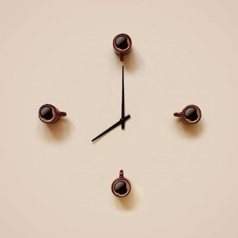 Pequeñas tazas marrones con café e indicadores negros que se colocan como la cara del reloj