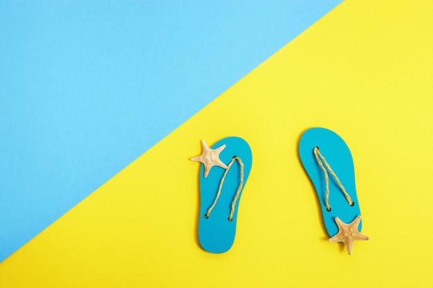 Pequeñas zapatillas de playa y estrellas de mar sobre papel brillante de color azul y amarillo, fondo de verano