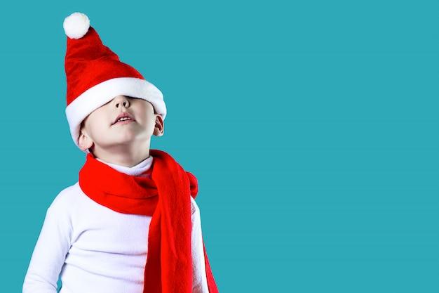 El pequeño y alegre gorro de papá noel cayó sobre sus ojos. un pañuelo rojo está atado alrededor de su cuello. sobre un fondo azul
