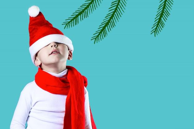 El pequeño y alegre gorro de papá noel cayó sobre sus ojos. un pañuelo rojo está atado alrededor de su cuello.