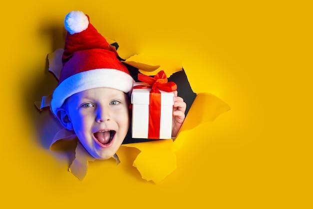 El pequeño y alegre papá noel hace un regalo, saliendo del irregular fondo amarillo brillante