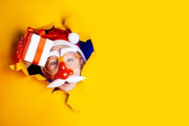El pequeño y alegre santa con gafas con nariz roja y bigote hace un regalo, saliendo del irregular fondo amarillo