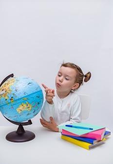 Un pequeño alumno se sienta en una mesa con libros de texto y señala un globo sobre un fondo blanco aislado. orientación vertical