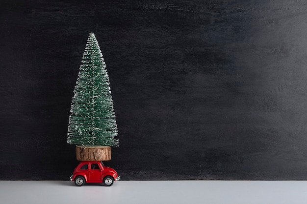 Pequeño árbol artificial en el techo del coche de juguete sobre fondo negro. entrega de árboles de navidad. copie el espacio.
