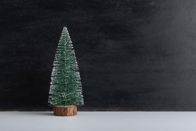 Pequeño árbol de navidad artificial sobre soporte de madera sobre fondo negro. fondo de año nuevo. copia espacio