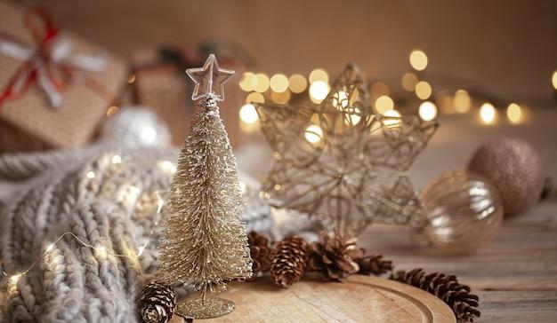 Pequeño árbol de navidad brillante decorativo en primer plano sobre un fondo borroso de adornos navideños, guirnaldas y luces bokeh.