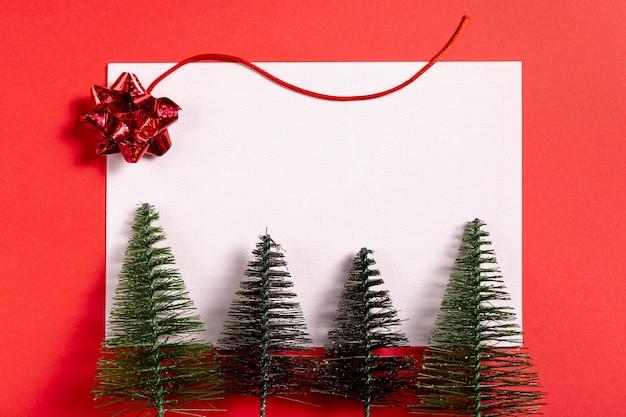 Pequeño árbol de navidad y hoja en blanco
