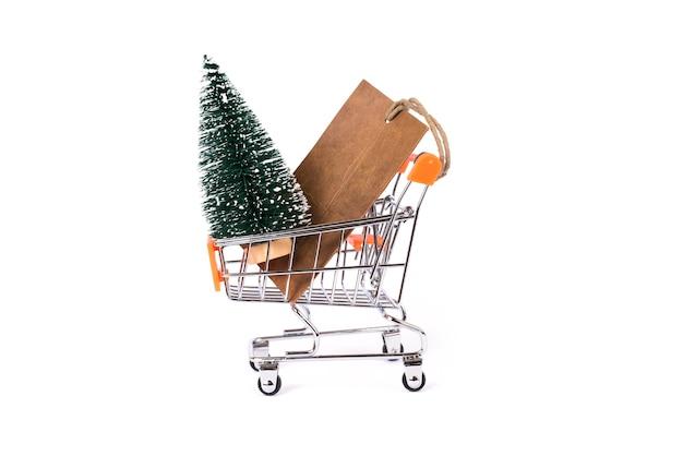 Pequeño árbol de navidad y precio de papel en el modelo de carro de compras aislado fondo blanco.