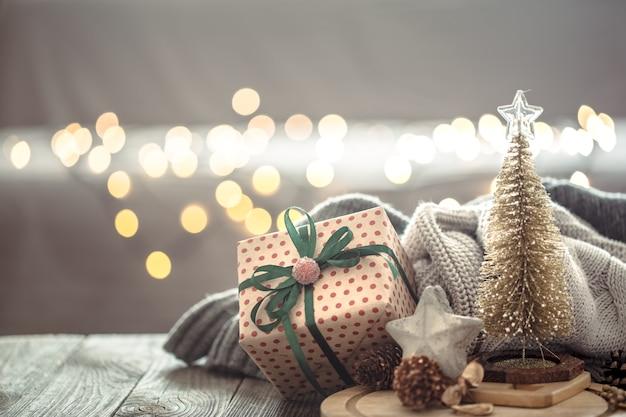 Pequeño árbol de navidad con presente sobre luces de navidad bokeh en casa sobre mesa de madera con suéter en una pared y adornos.