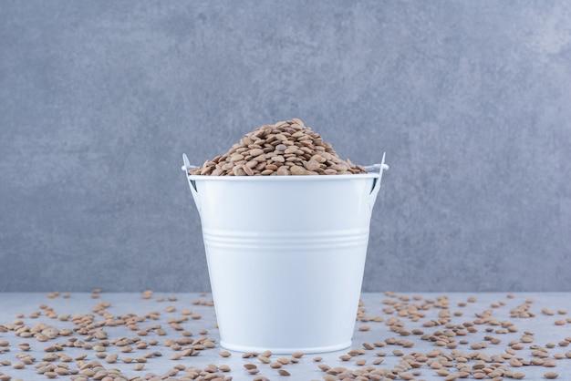 Pequeño balde de lentejas marrón sentado en medio de granos esparcidos sobre la superficie de mármol