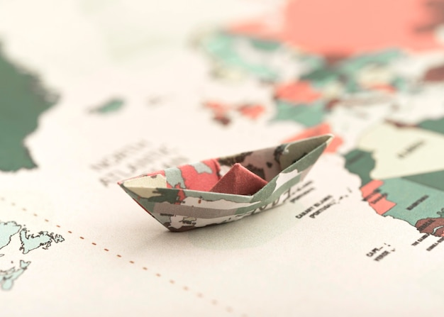 Pequeño barco de origami en el mapa del mundo