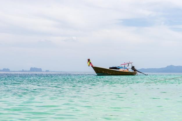 Pequeño barco turístico de madera anclado en la playa con vista de cielo nublado blanco