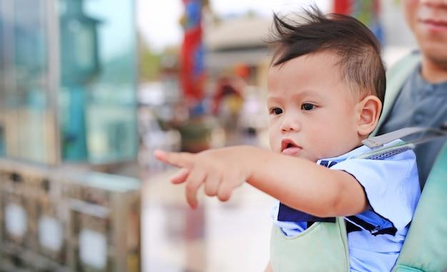 El pequeño bebé adorable que señala algo con el padre lleva por el hipseat al aire libre. de cerca.