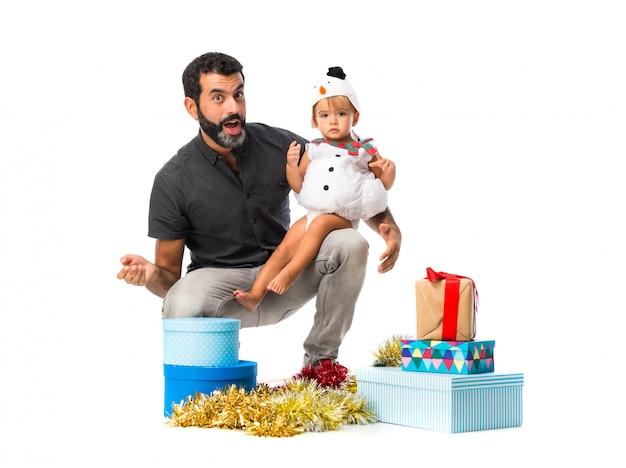Pequeño bebé adorable con su padre en las fiestas de navidad en fondo blanco aislado