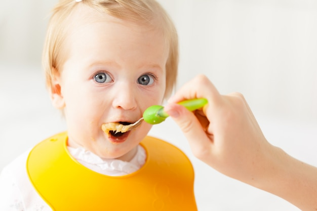 Pequeño bebé alimentándose con una cuchara