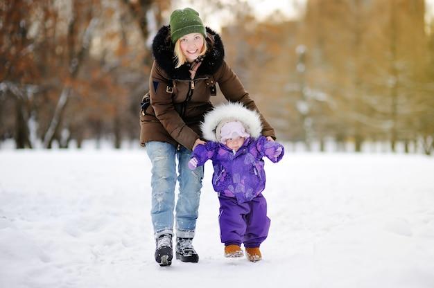 Pequeño bebé aprendiendo a caminar. mujer joven con su niña pequeña en el parque de invierno