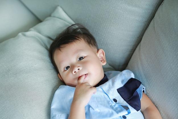 Pequeño bebé asiático adorable que chupa el finger en la boca que miente en el sofá gris.