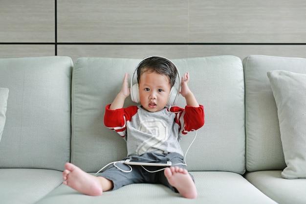 Pequeño bebé asiático lindo en auriculares está usando un teléfono inteligente