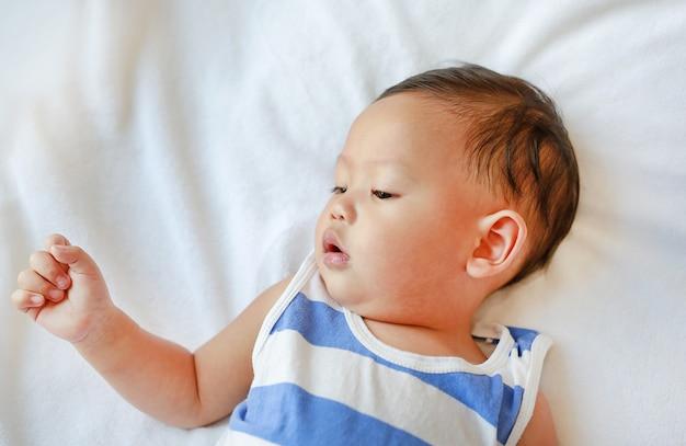 Pequeño bebé asiático del retrato que miente en la cama blanca.