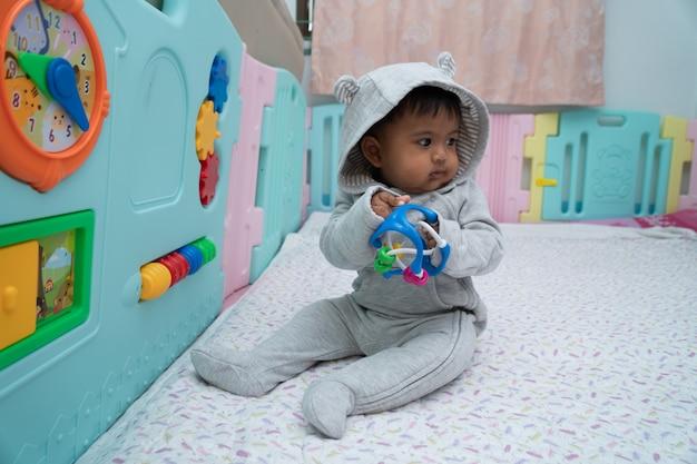Pequeño bebé asin lindo que se sienta y juega el juguete en el cuarto