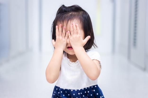 El pequeño bebé bebé sentado en el suelo llorando y se cubre la cara con la mano