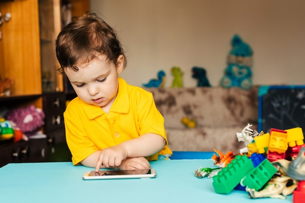 Pequeño bebé caucásico usa teléfono inteligente en casa
