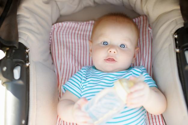 Pequeño bebé en cochecito con una botella de agua en el día de verano