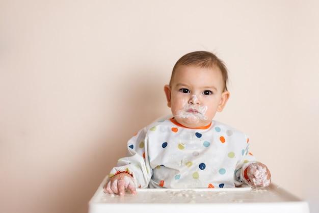 Un pequeño bebé comiendo su cena y haciendo un lío con yogur y cereales.