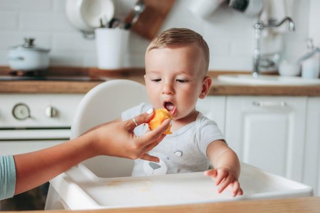Pequeño bebé encantador que come el primer melocotón de la comida en la cocina.