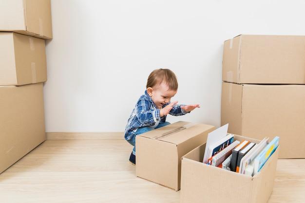 Pequeño bebé feliz que juega con las cajas de cartón en el nuevo hogar