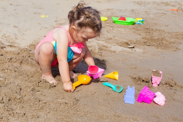 Pequeño bebé feliz en el traje de baño que juega en la arena en la playa en un día caliente soleado.