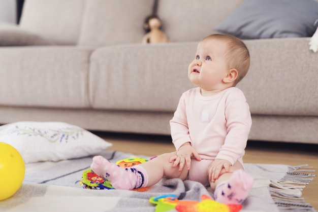 Pequeño bebé hermoso se sienta en el suelo y juega