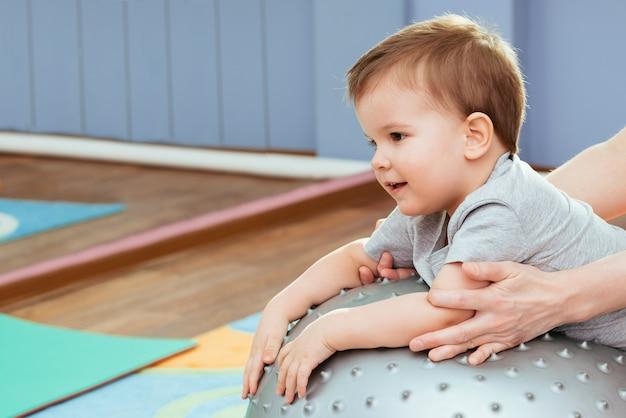 Pequeño bebé juega con un fitball en el gimnasio.