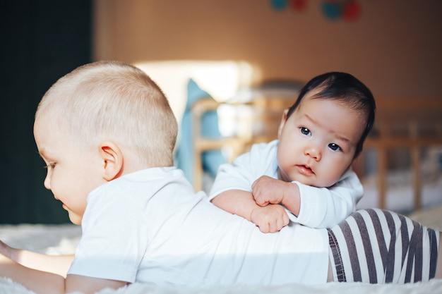 Pequeño bebé lindo con el hermano mayor que miente en cama en casa