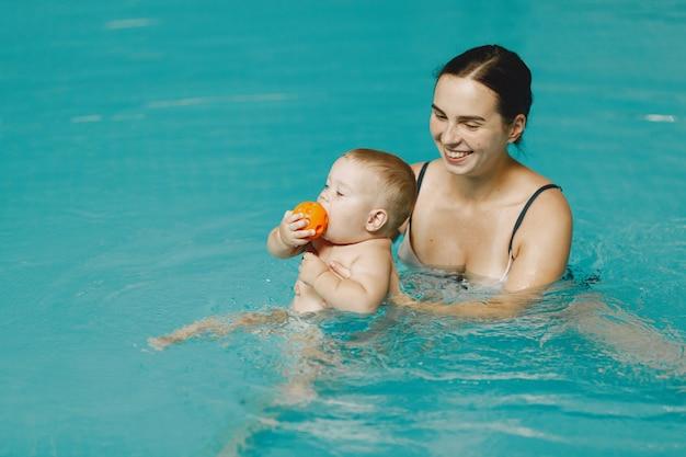 Pequeño bebé lindo. madre con hijo. familia jugando en un agua