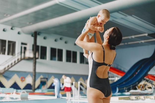 Pequeño bebé lindo. madre con hijo. familia jugando junto al agua