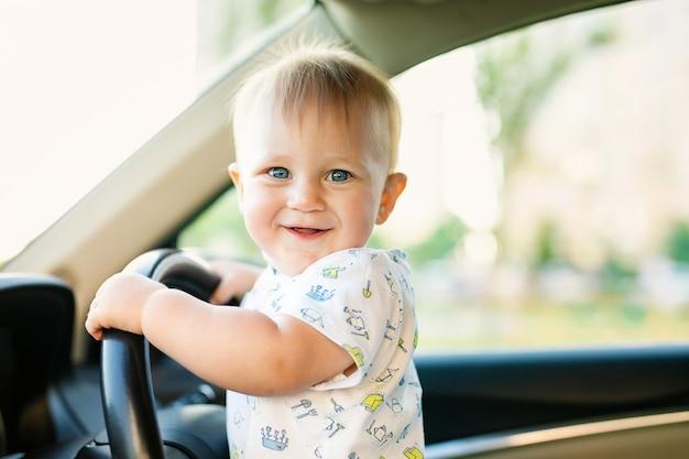 Pequeño bebé lindo que conduce el coche grande, sosteniendo el volante, sonriendo y mirando adelante con interés.